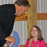 a young girl smiling at a man holding a fan