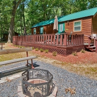 outside of cabin with porch and fire pit