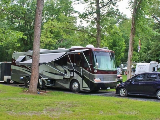 gray and black camper with car at campsite