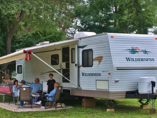 family sitting outside of camper during the day