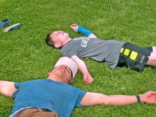 boys resting on grass