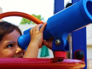 child looking through telescope at playground