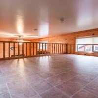 Loft with tile floor and railing in cabin