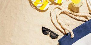 beach sand with sunglasses, sandals and a beach bag